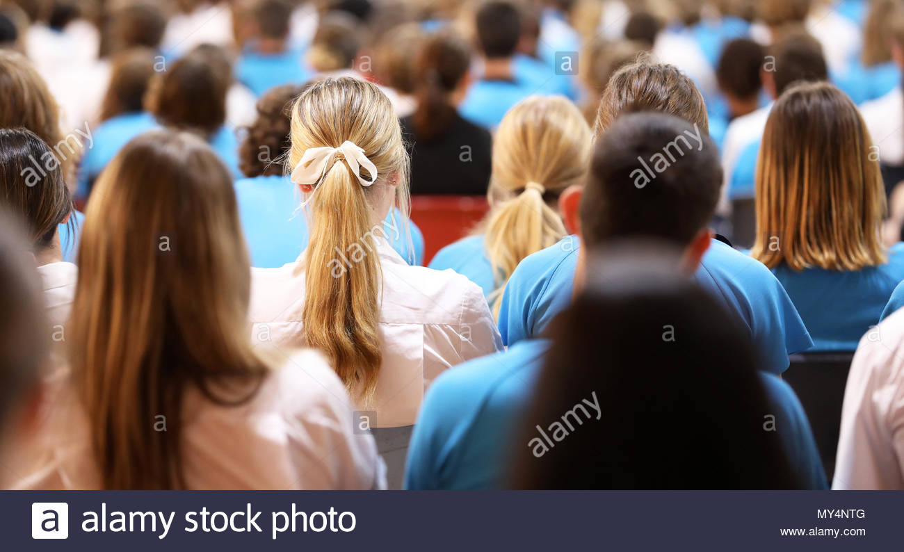 Crowd of students at high school assembly in the audience. Listening attentively in the school hall. Education concept, learning, teaching, kids at sc - Stock Image