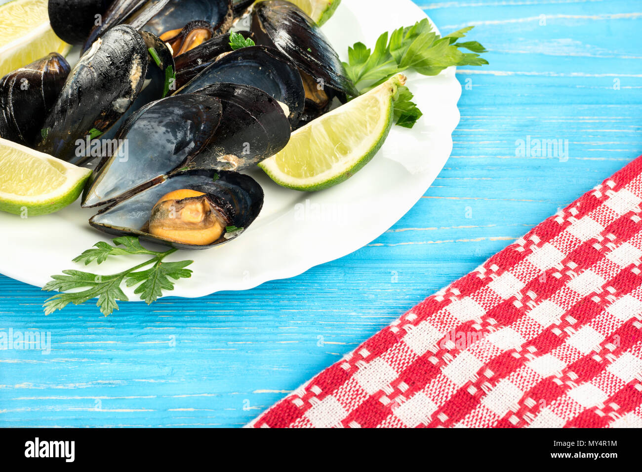 Delicious cooked mussels in a plate on a blue table - Stock Image