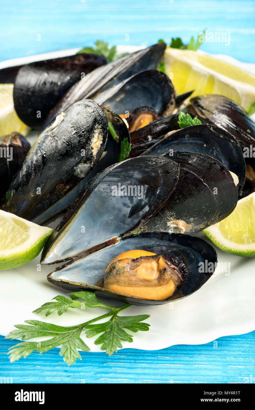 Cooked mussels with lime slices on a plate, close-up - Stock Image