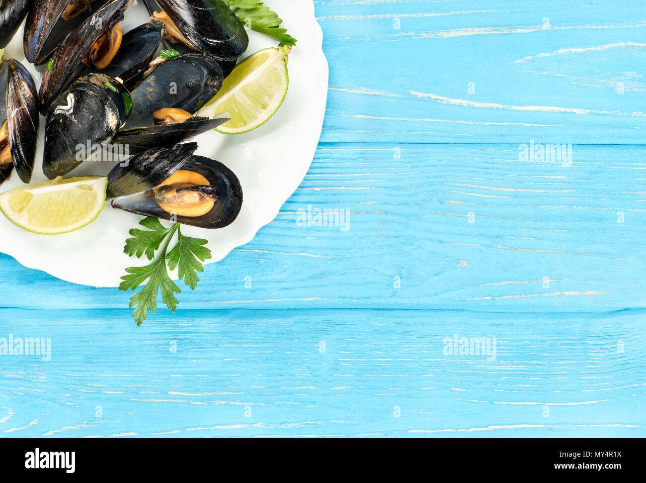 Part of a white plate with cooked mussels on a blank wooden background - Stock Image