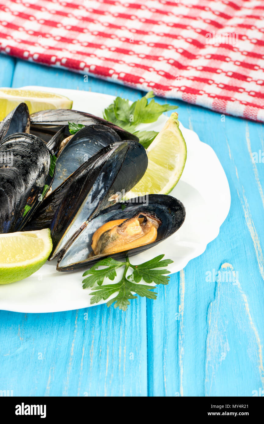 Delicious mussels in the shell on a plate and table - Stock Image