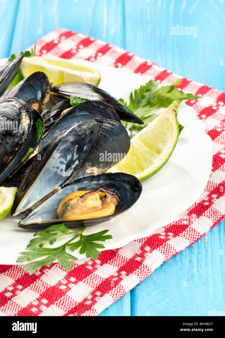 Part of dish with cooked mussels and lime on the plate and on the towel - Stock Image