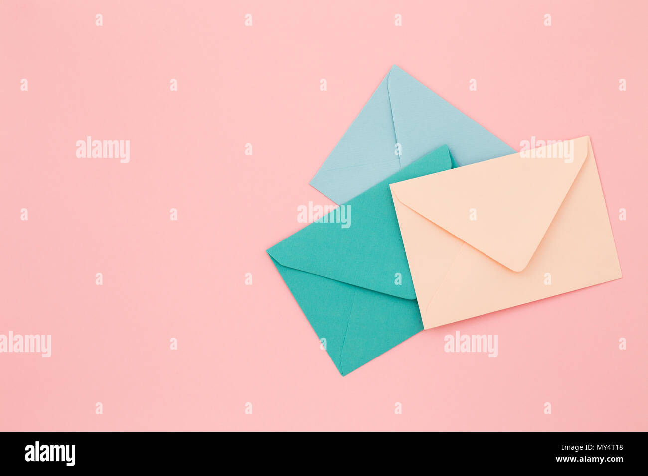 Three colored envelopes on pink background. Minimalist styled composition, top view, correspondence concept. - Stock Image