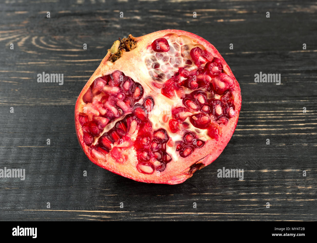Juicy half of pomegranate on a dark table - Stock Image