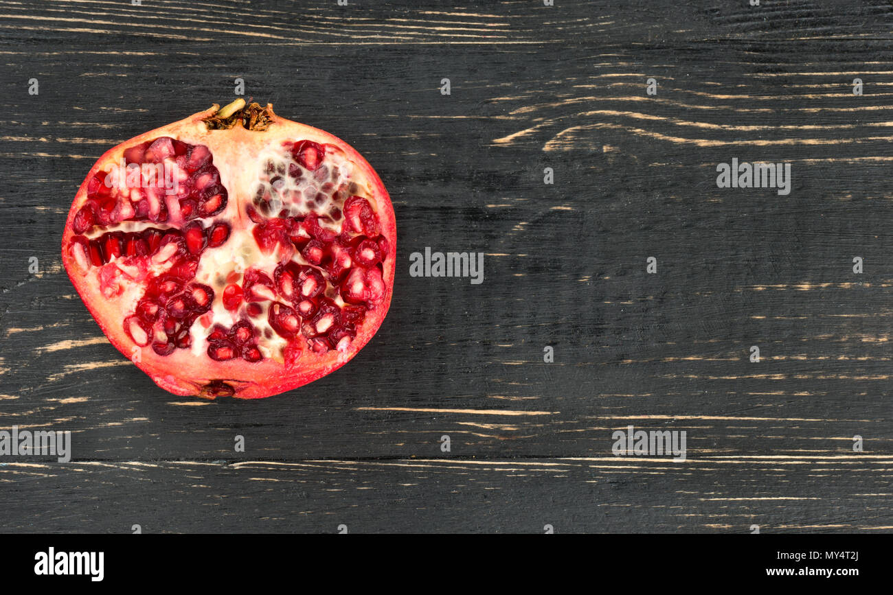 Juicy half of pomegranate on a blank wooden background - Stock Image