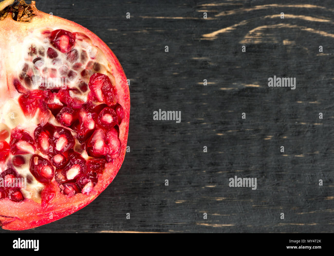 Part of half a pomegranate on a dark table closeup - Stock Image