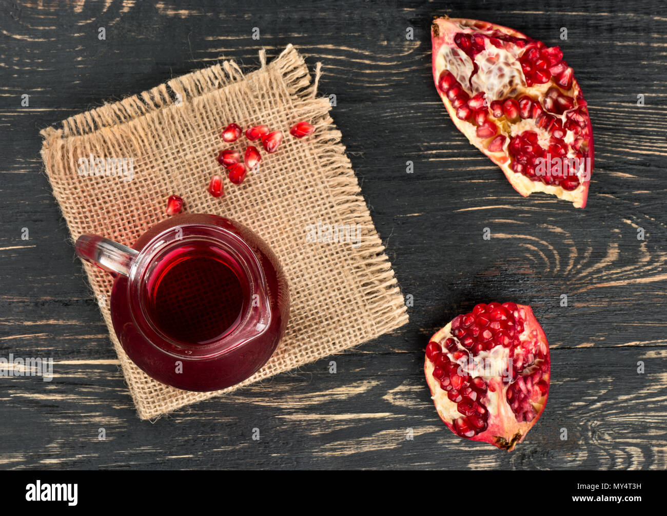 Delicious pomegranate juice with slices and beans on sackcloth and table - Stock Image