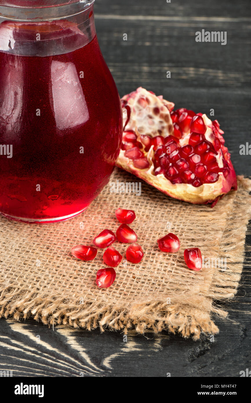 Pomegranate juice in a glass with grains on the sacking and table - Stock Image