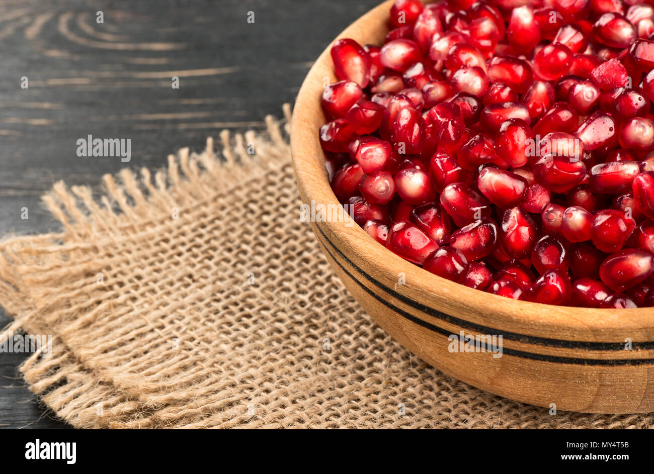 Part bowl filled with pomegranate seeds on sacking close-up - Stock Image