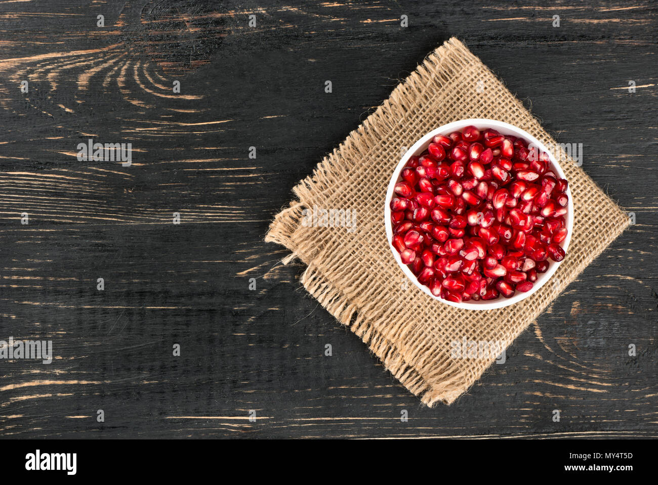 Bowl with pomegranate seeds on sackcloth and table top view - Stock Image
