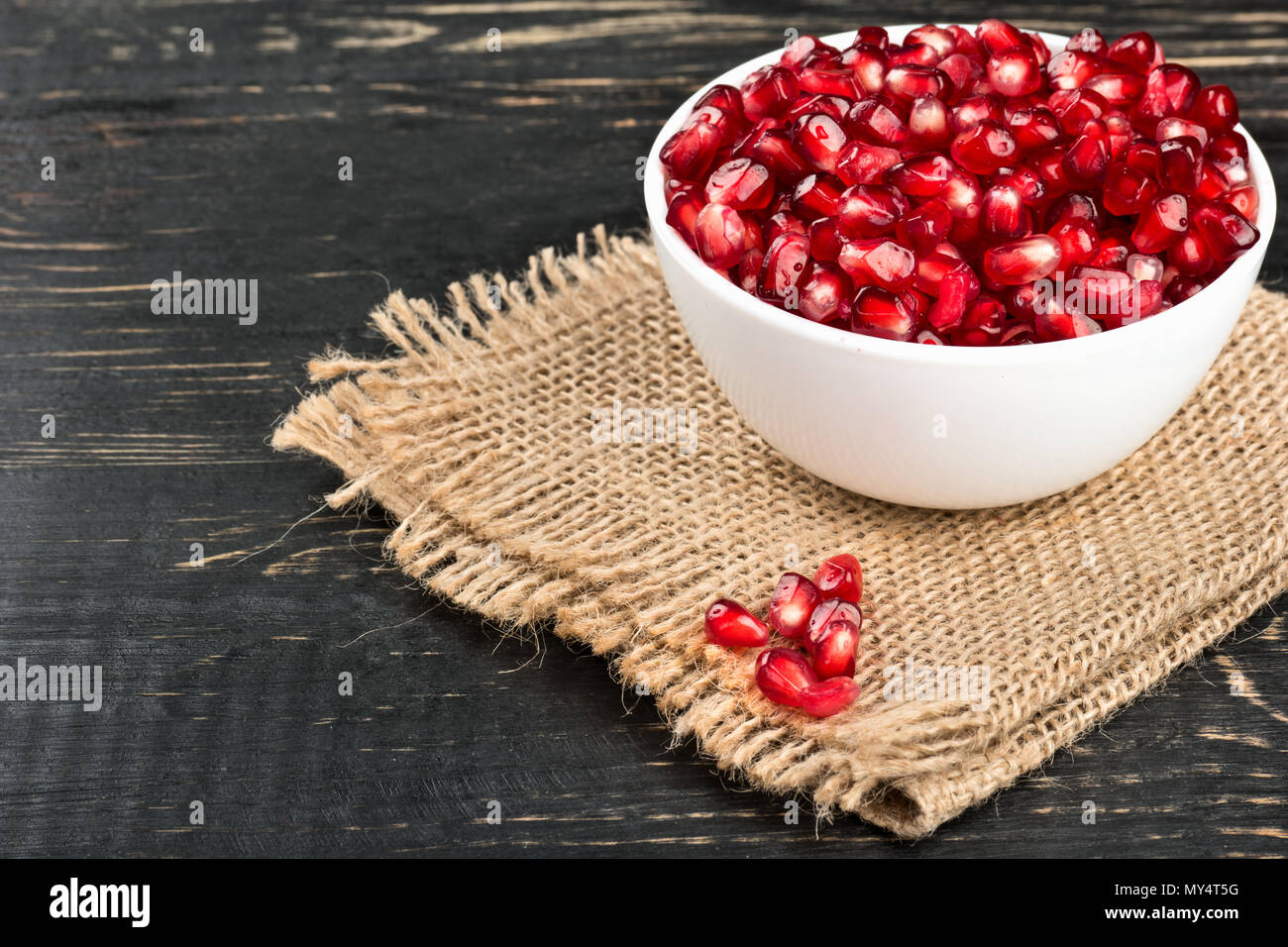 Ceramic bowl filled with pomegranate seeds on sackcloth and table - Stock Image