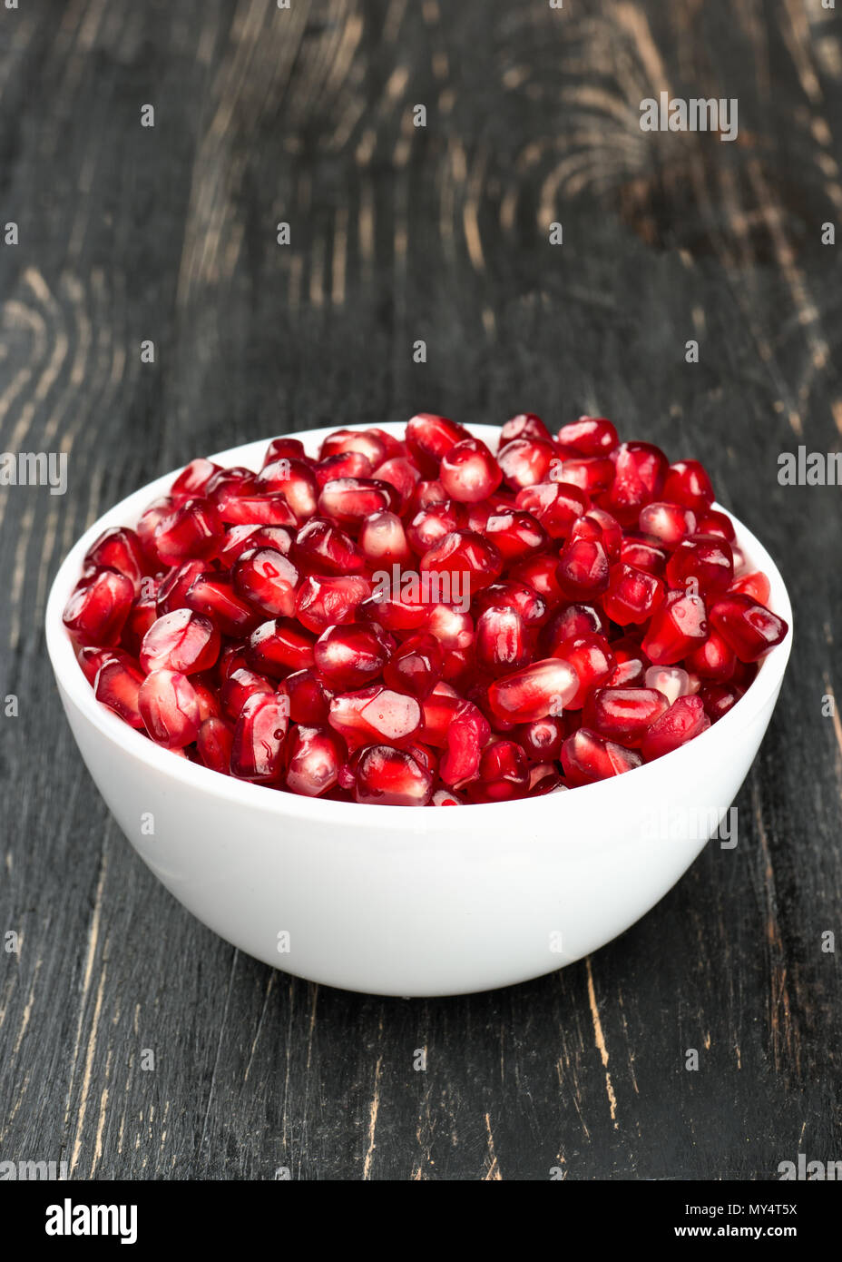 White bowl filled with pomegranate seeds on a wooden background close up - Stock Image