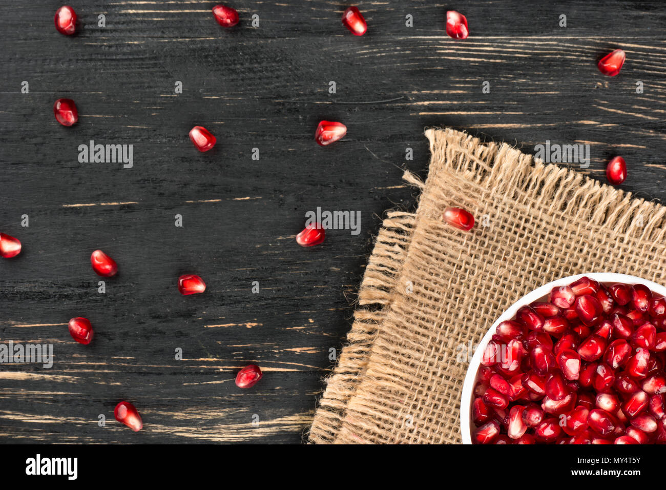 Part of the bowl with pomegranate seeds on sackcloth and table, top view - Stock Image