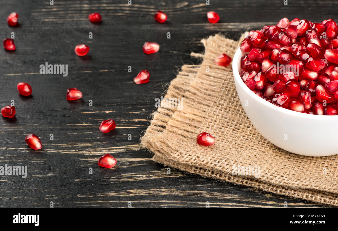 Part of the bowl with pomegranate seeds on sackcloth and table - Stock Image