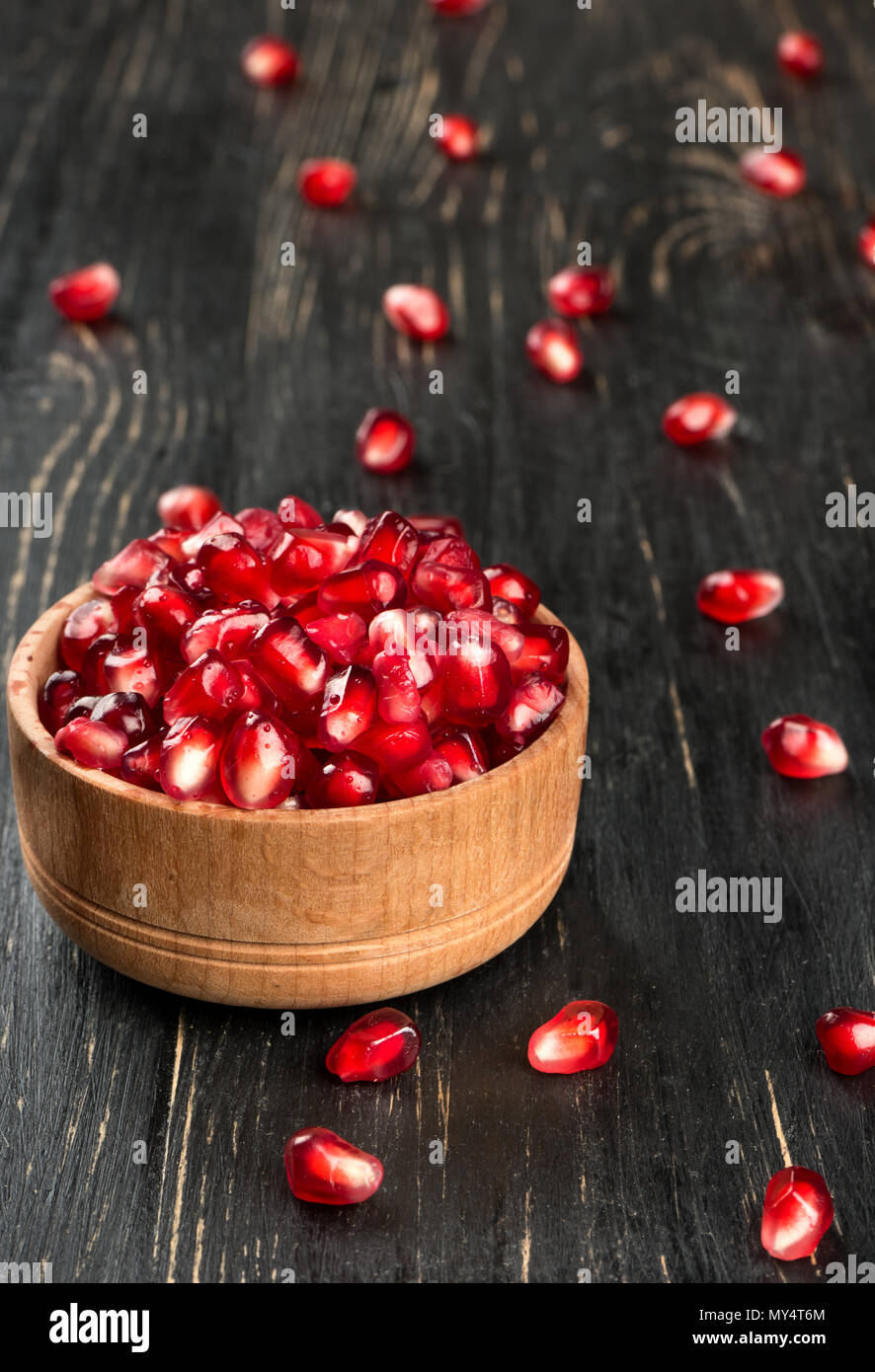 Fresh pomegranate seeds in a bowl and scattered on the table - Stock Image
