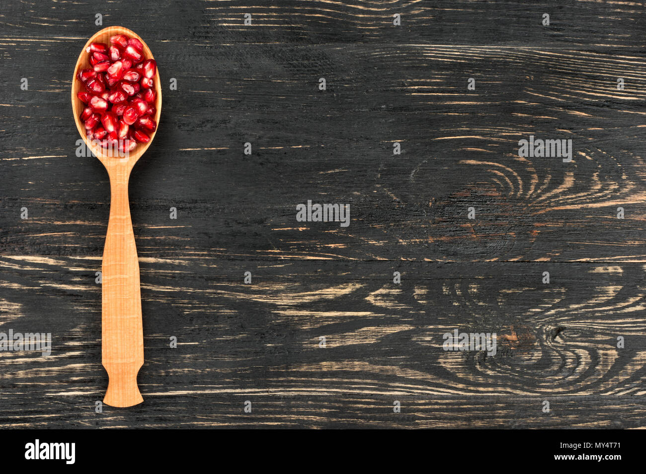 Pomegranate seeds in spoon on a blank wooden background, top view - Stock Image