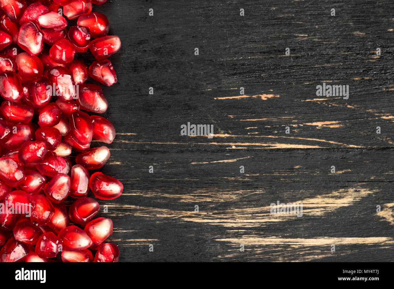 Scattered pomegranate seeds on a blank wooden background - Stock Image