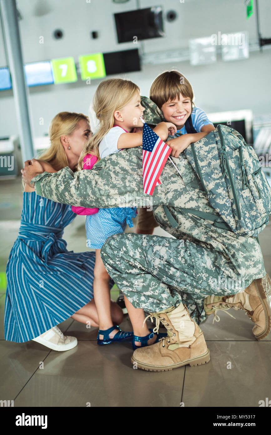 family hugging man in military uniform while meeting at airport - Stock Image