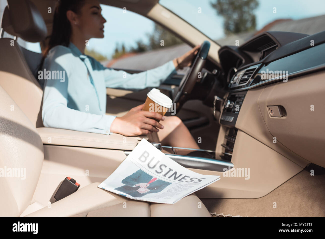 Young woman driving a car with business newspaper lying in front seat - Stock Image