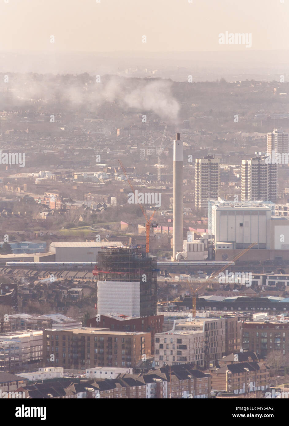 London, England, UK - February 27, 2015: A SouthEastern commuter train passes the chimney of the South East London Combined Heat and Power plant in Be - Stock Image
