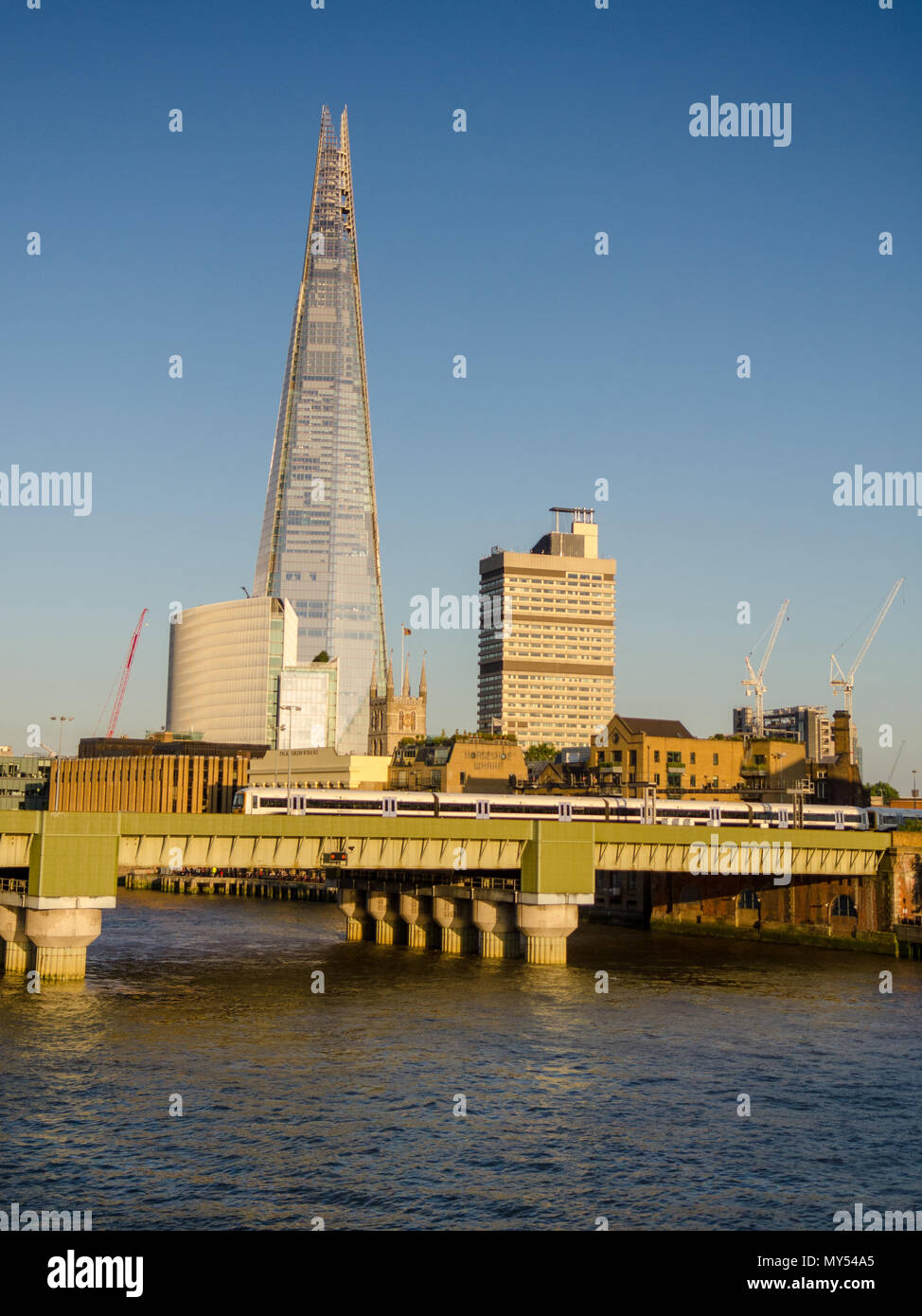 London, England, UK - June 10, 2015: A SouthEastern commuter train crosses the River Thames into London Cannon Street railway station with a backdrop  - Stock Image
