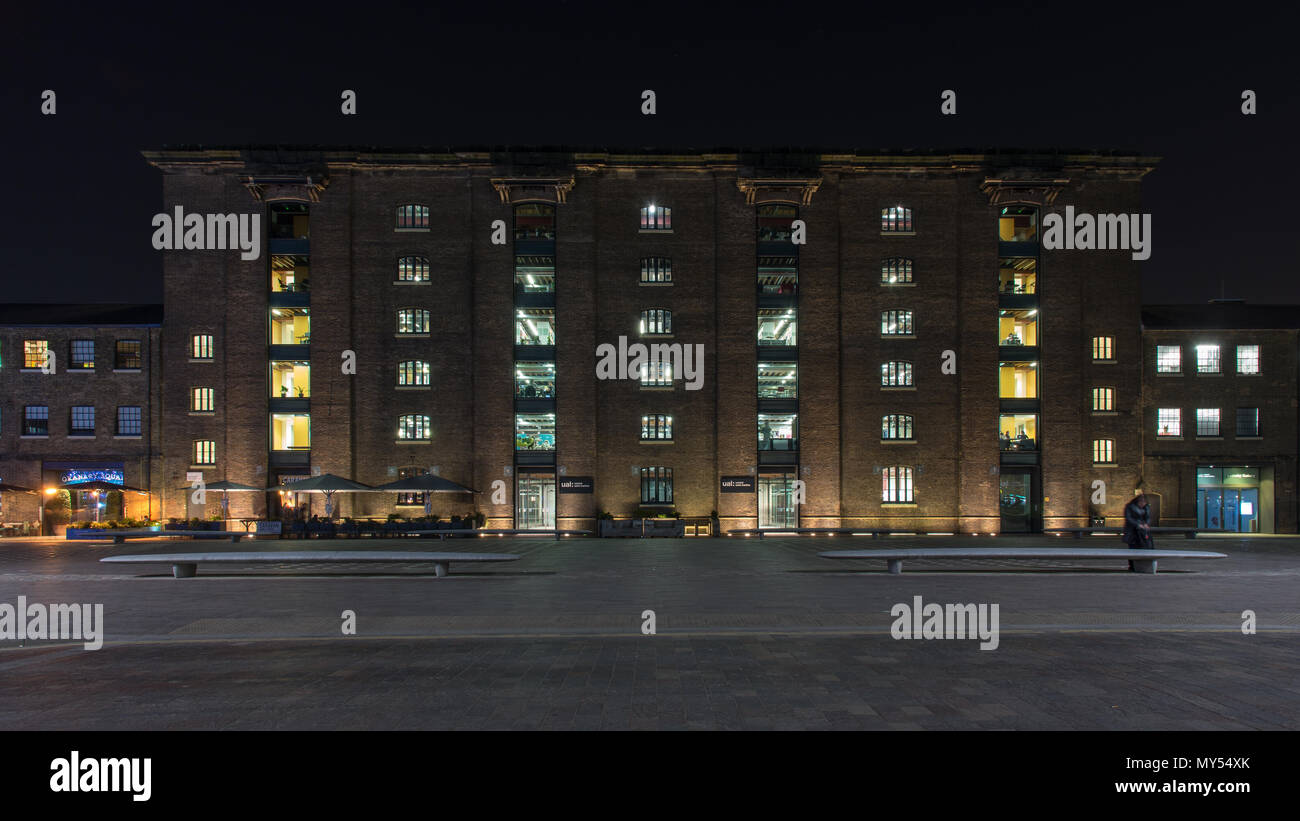 London, England, UK - February 22, 2018: Central St Martin's College, part of the University of the Arts, is lit up at night in Granary Square, part Stock Photo