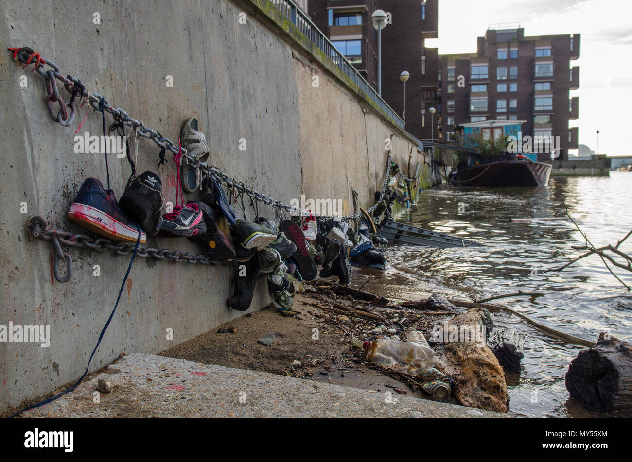 London, England, UK - January 14, 2014: Shoes found littering the tidal shores of the River Thames are strung up along the embankment of Battersea Riv - Stock Image