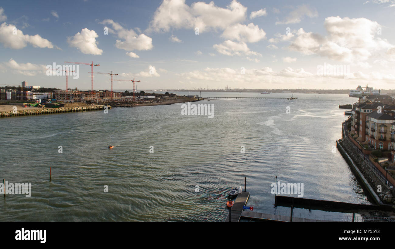 The River Itchen flows into Southampton Water between apartment buildings and construction sites in the city of Southampton. - Stock Image