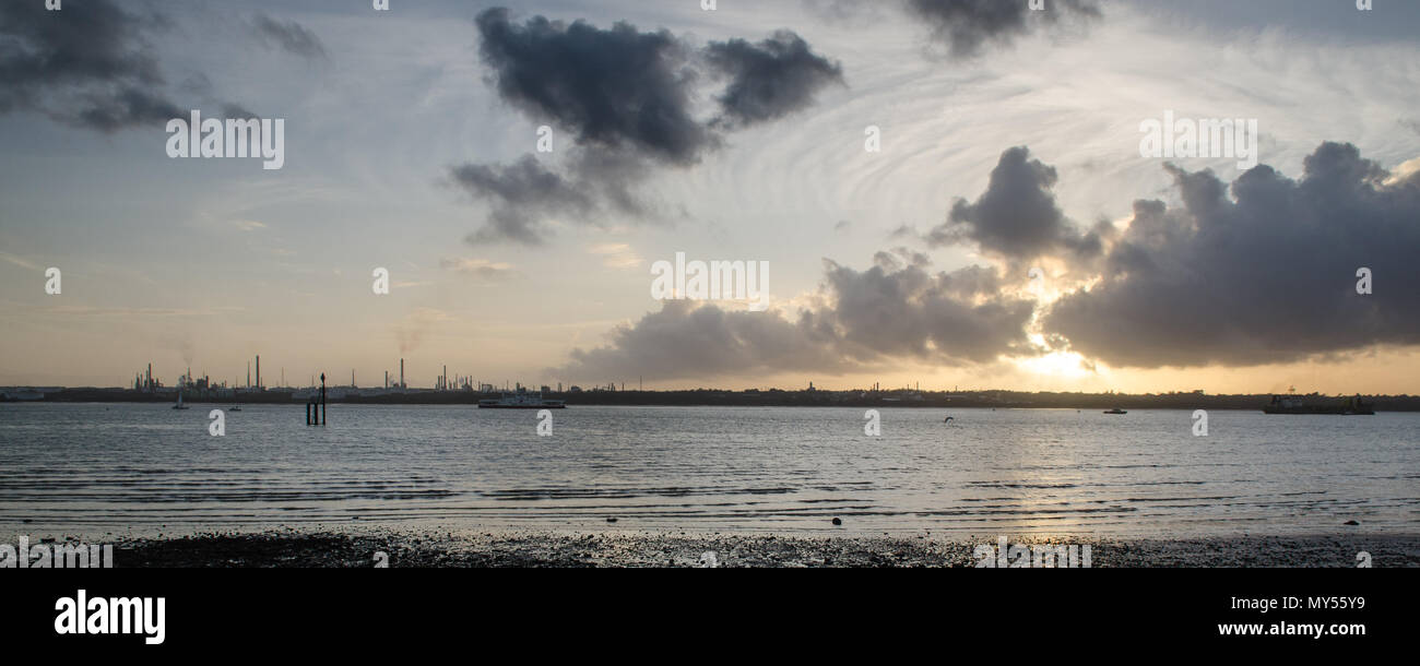 The sunset silhouettes the industrial towers of Fawley oil refinery on the shores of Southampton Water, seen from Netley. - Stock Image
