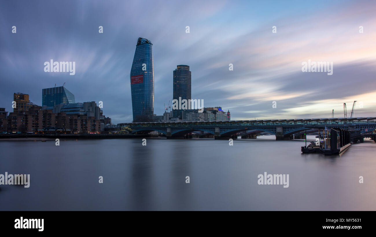 London, England, UK - April 3, 2018: The River Thames flows under Blackfriars railway station, with the South Bank skyline behind at sunset. - Stock Image