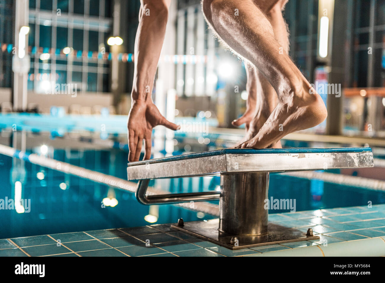 cropped view of swimmer standing on diving board ready to jump into competition swimming pool - Stock Image
