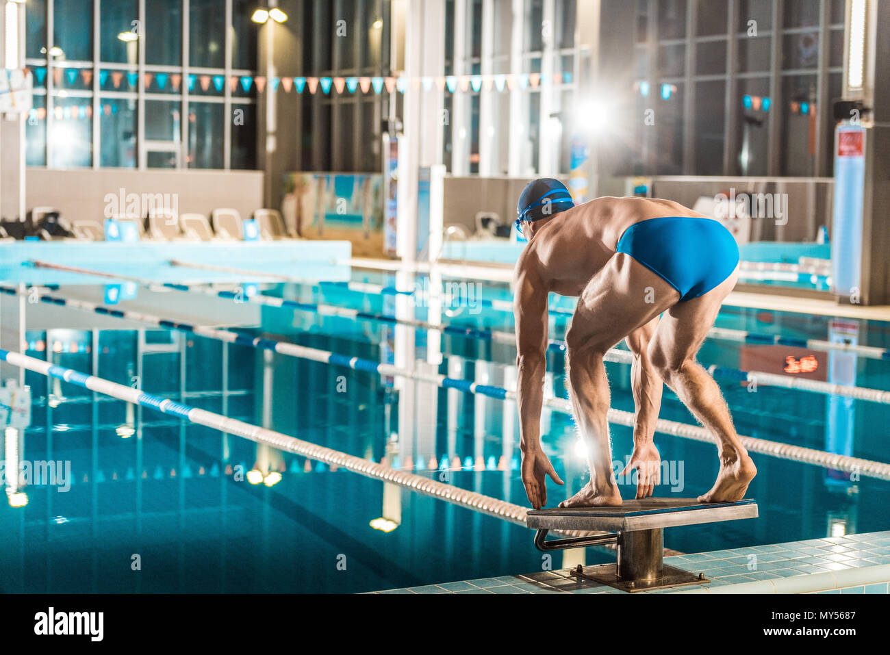 swimmer standing on diving board ready to jump into competition swimming pool - Stock Image