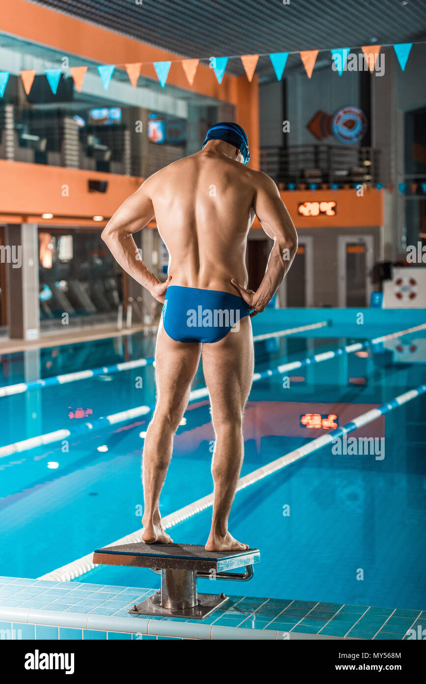 back view of muscular swimmer in swimming trunks standing at swimming pool - Stock Image