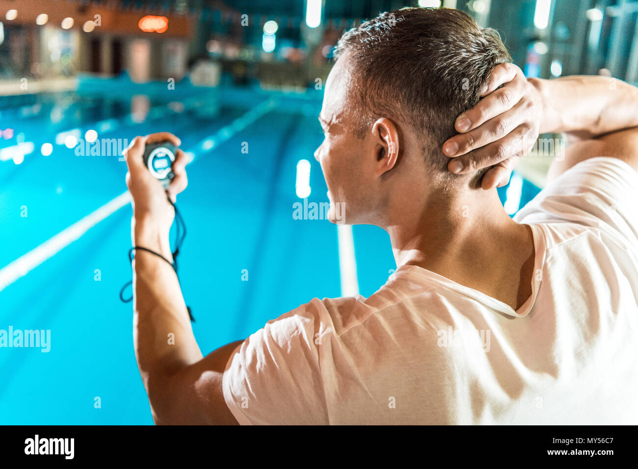handsome swim trainer with timer standing at competition ...