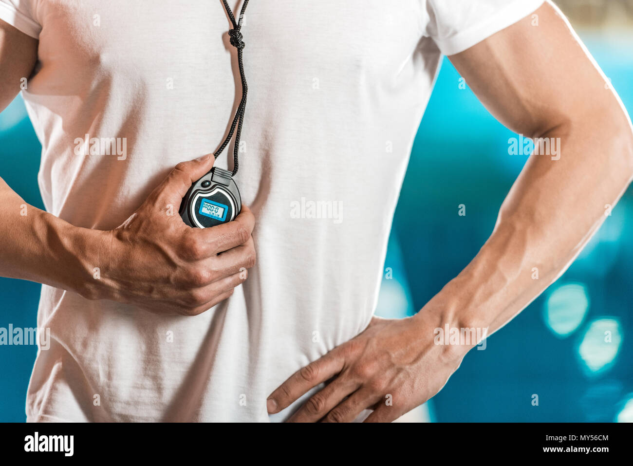 cropped view of swim trainer with stopwatch at swimming pool - Stock Image
