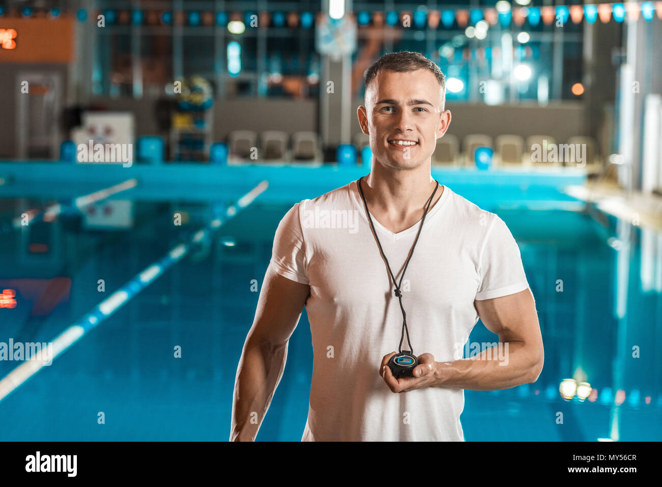 handsome swim trainer with stopwatch at competition swimming pool - Stock Image