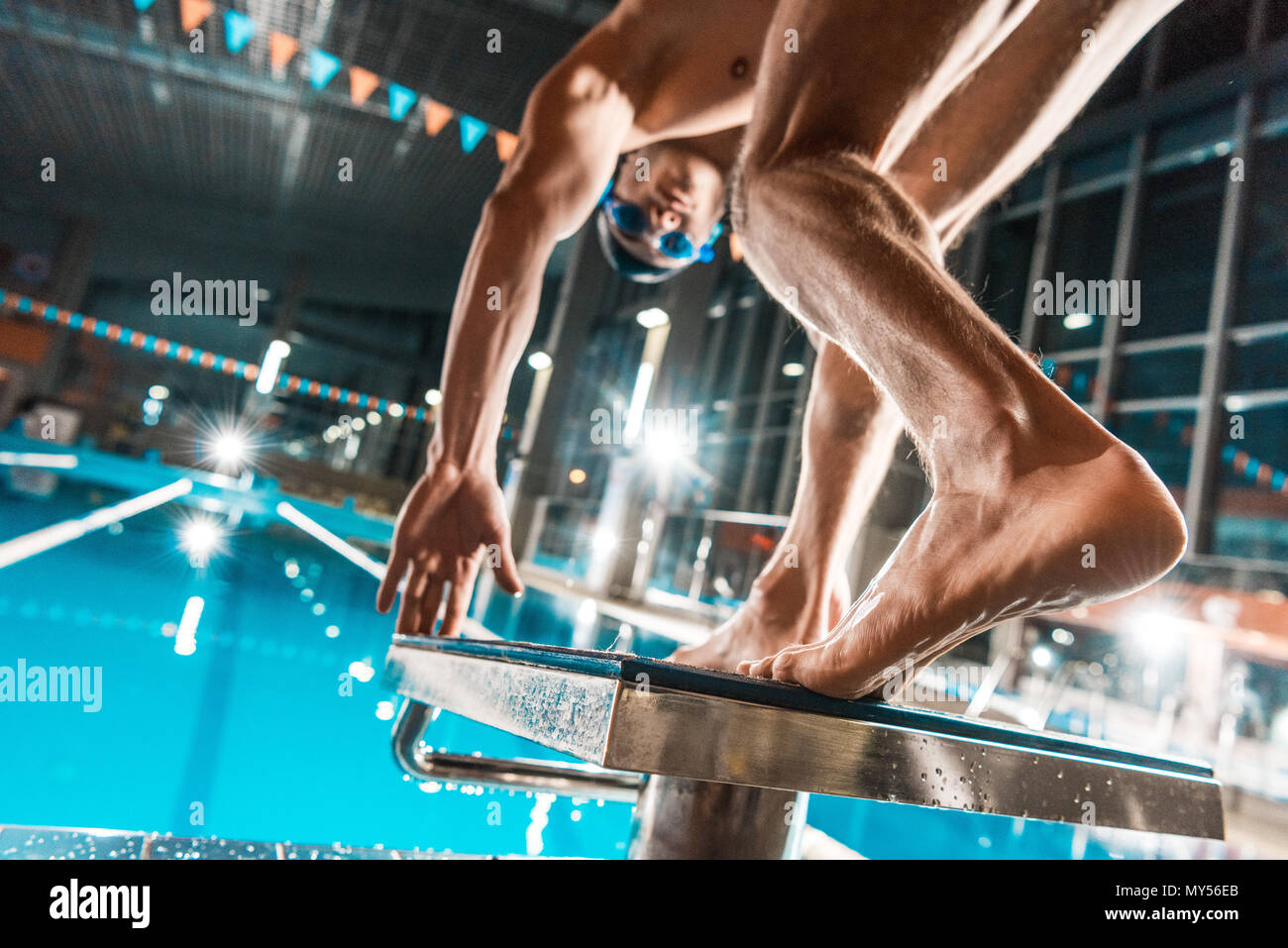 bottom view of swimmer jumping into competition swimming pool - Stock Image