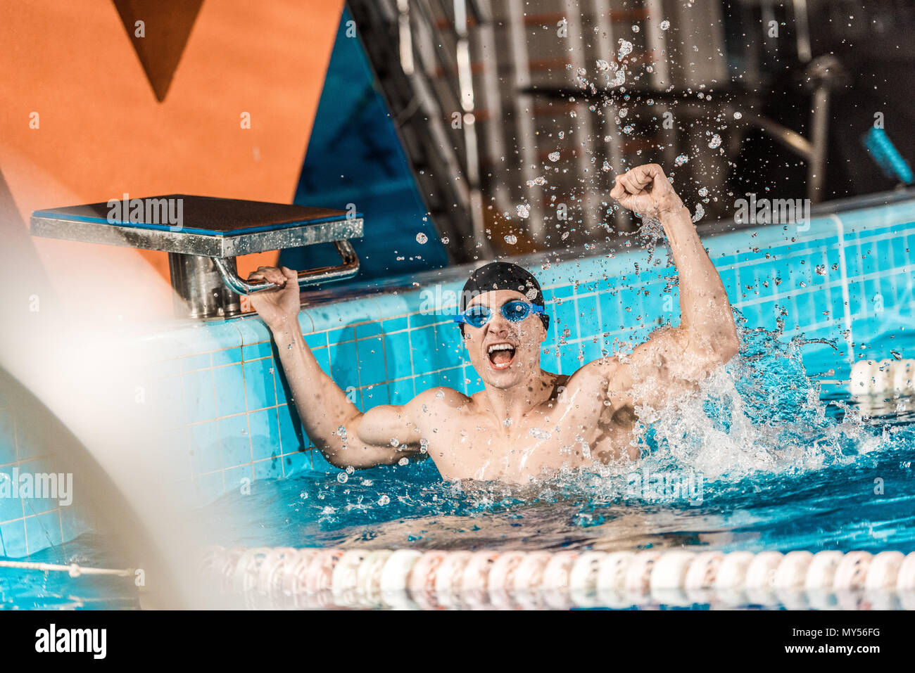 excited male winner in competition swimming pool - Stock Image