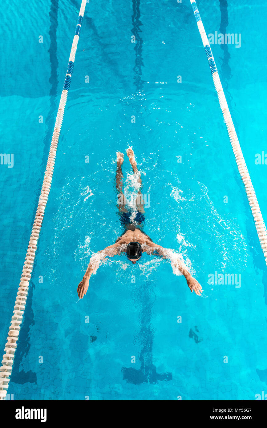 athletic swimmer in cap and goggles swimming in pool - Stock Image