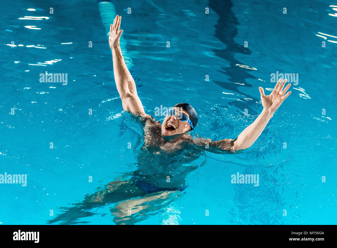 excited swimmer in goggles gesturing in competition swimming pool - Stock Image