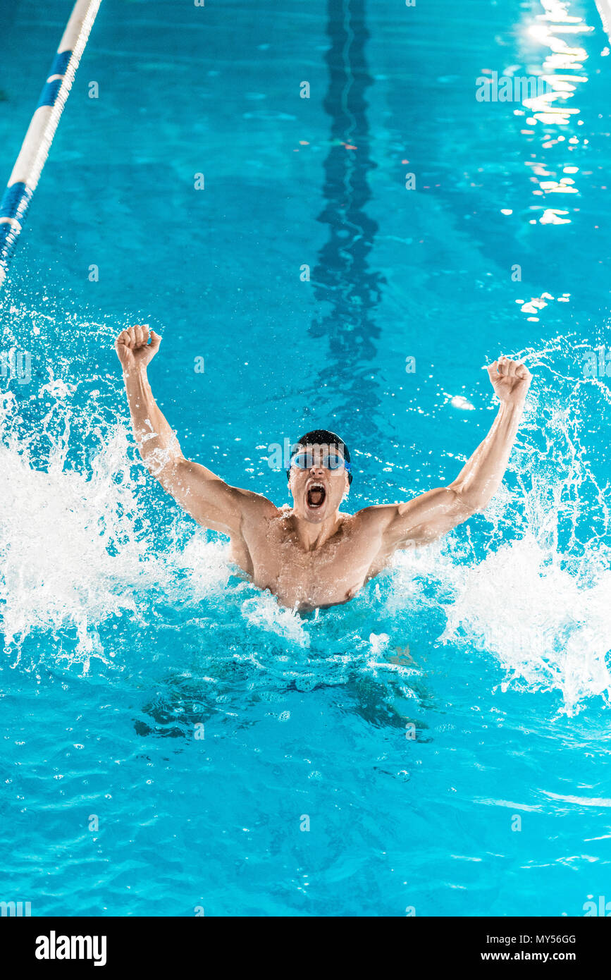 excited swimmer gesturing and making splash in competition swimming pool - Stock Image