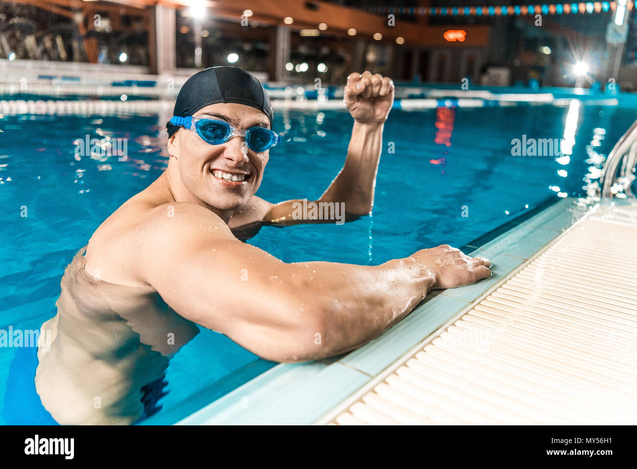 smiling swimmer gesturing and win in swimming pool - Stock Image