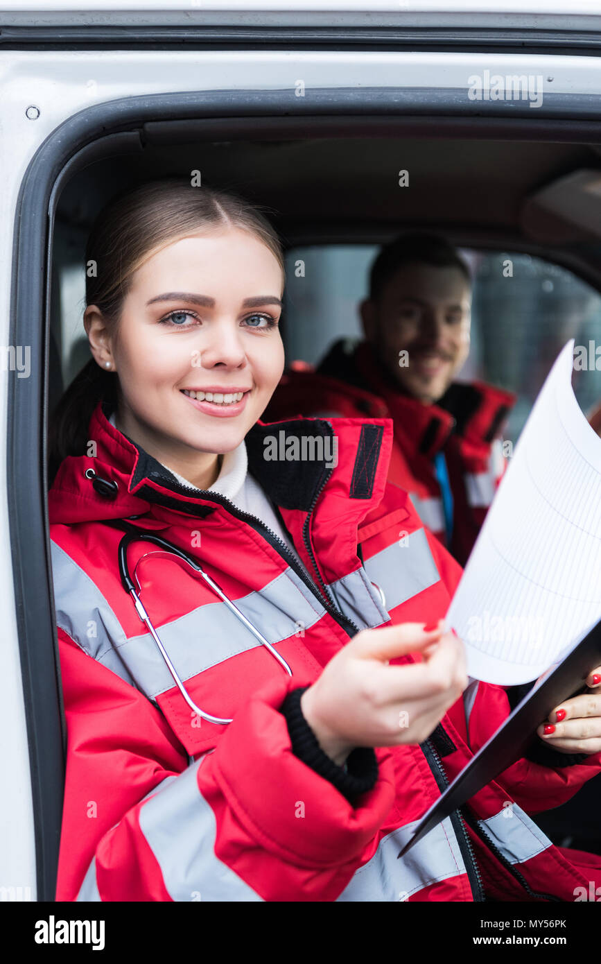 smiling young female paramedic holding clipboard and looking at camera - Stock Image