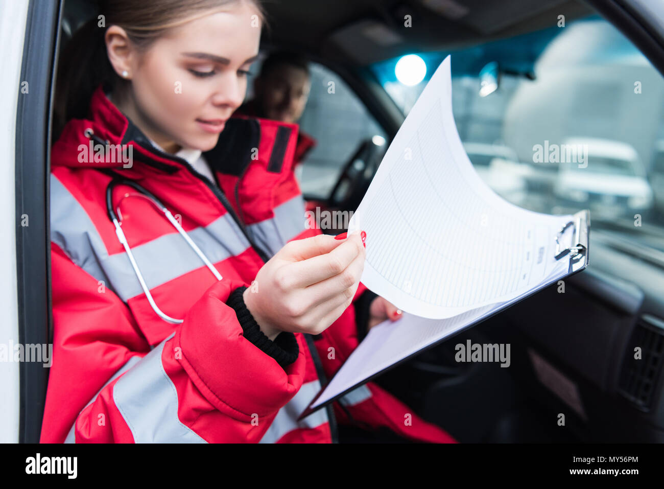 female paramedic sitting in ambulance and looking at clipboard - Stock Image