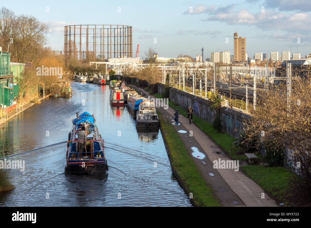 London, England - January 30, 2016: A traditional narrowboat navigating the Grand Union Canal at Old Oak Common, an industrial district and major rede - Stock Image