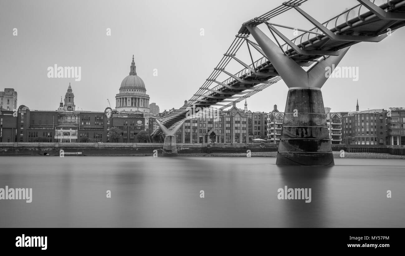 London, England, UK - May 29, 2018: The Millennium Bridge crosses the River Thames with St Paul's Cathedral and office buildings of the City of London - Stock Image