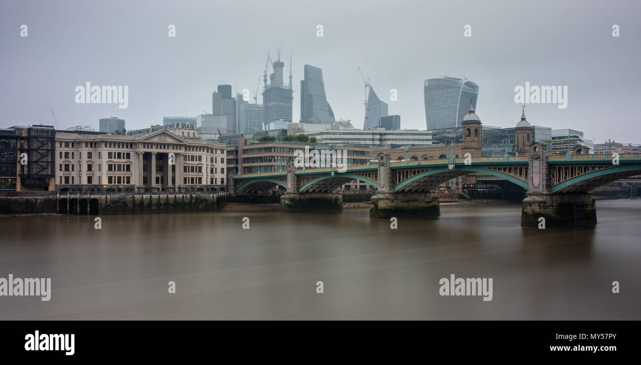 London, England, UK - May 29, 2018: Grey skies and air pollution shroud the City of London skyline viewed across the River Thames from beside Southwar - Stock Image