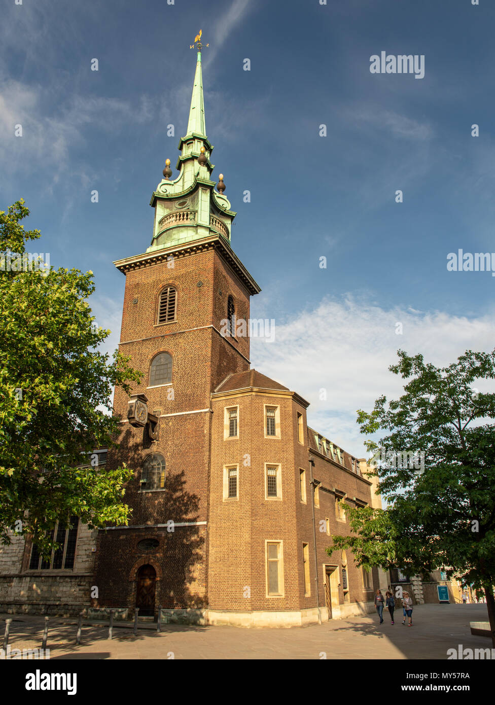 London, England, UK - June 1, 2018: Evening sun lights up the tower and spire of All Hallows by the Tower church in the City of London. - Stock Image