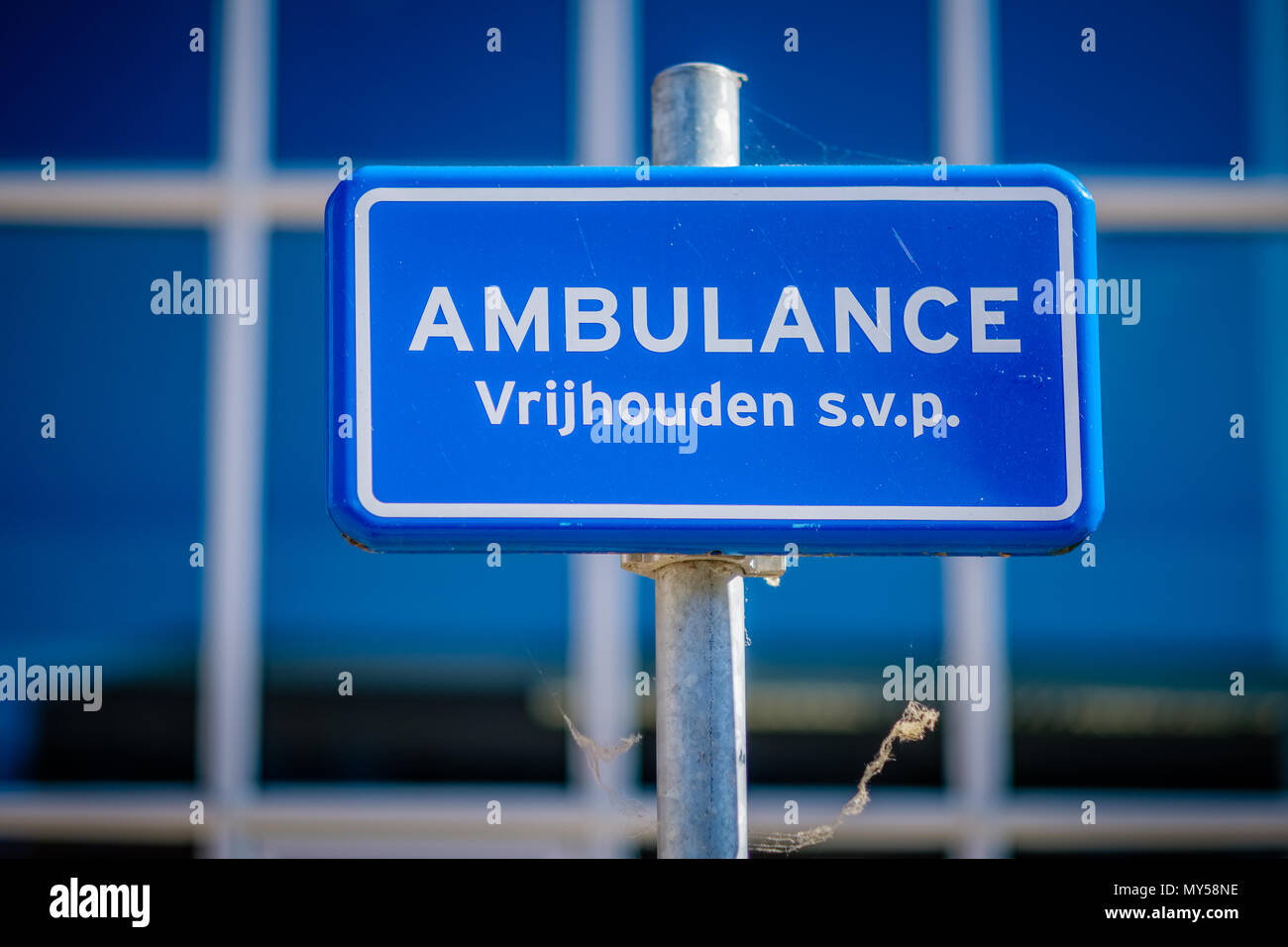 This sign near a Dutch public building prohibits parking at this space, at all times it has to be kept clear because it is in use by an ambulance. - Stock Image