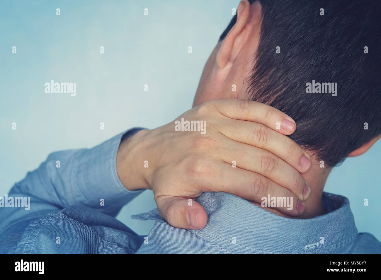 Close up of young man hand on his neck - neck pain concept. a fracture of the cervical vertebrae. young man holds his hand on the neck on a blue backg - Stock Image